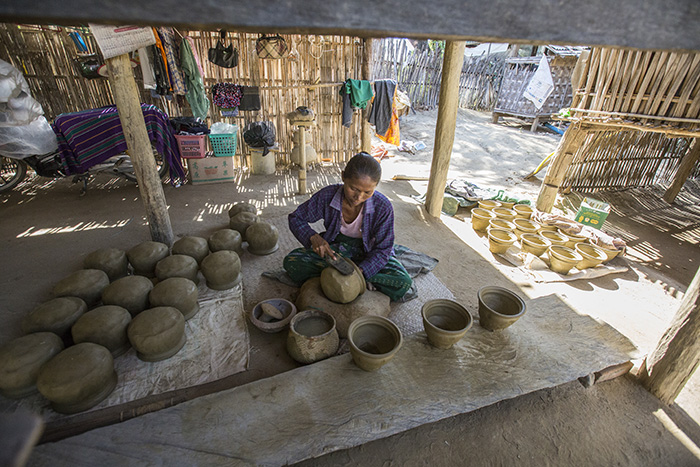 Khin Mar Cho works on a pot – one of two successful businesses she runs.