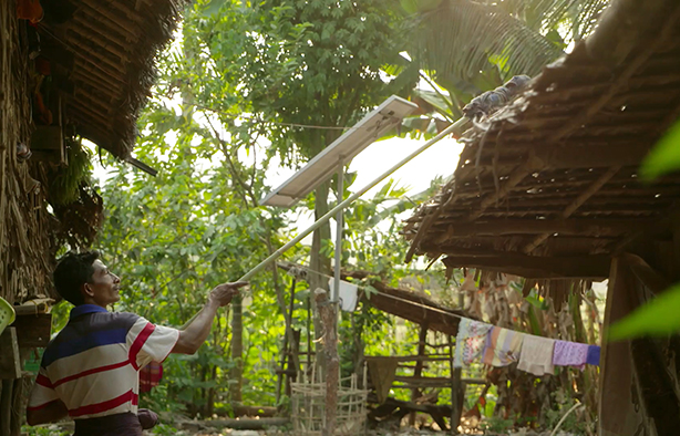 U Kyaw Htay maintains a solar panel by wiping it clean.