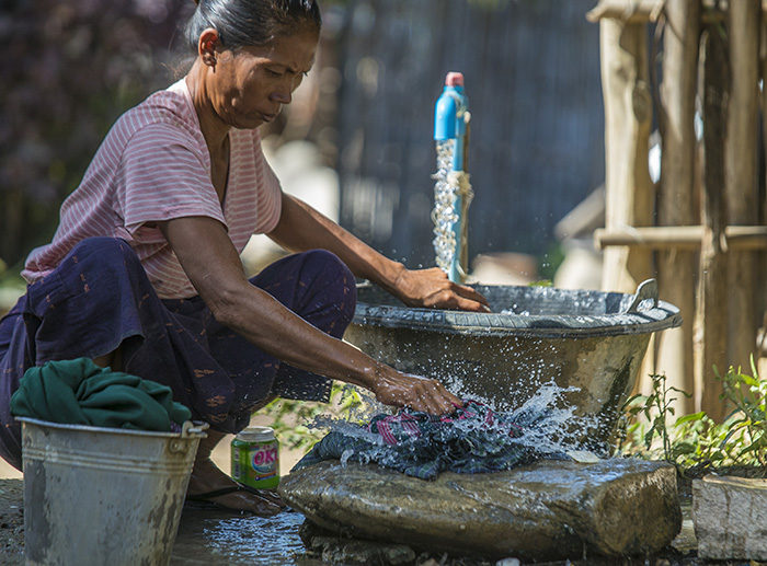 Khin Mar Cho washes laundry using her family's new water tap.