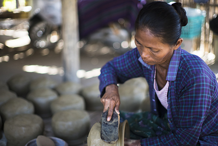 Khin Mar Cho works on a clay pot at her family's home.