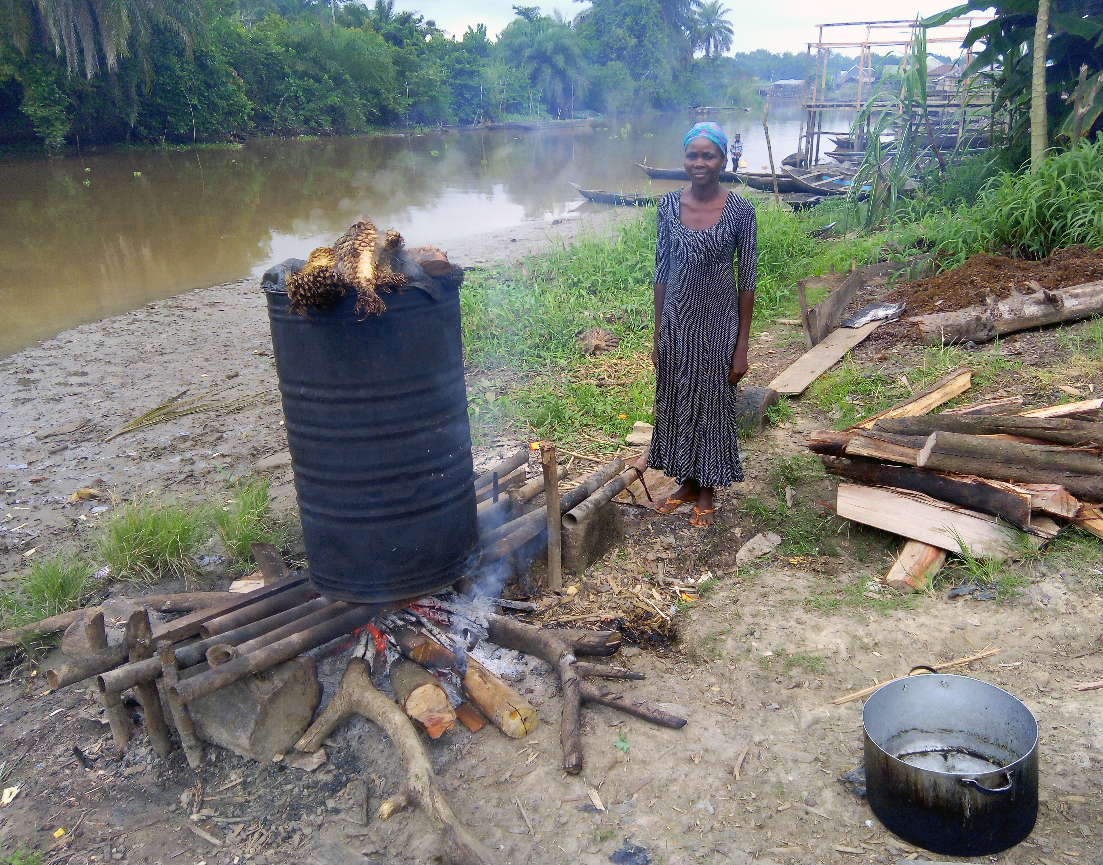 Boumono labors by the fire as she processes palm oil.