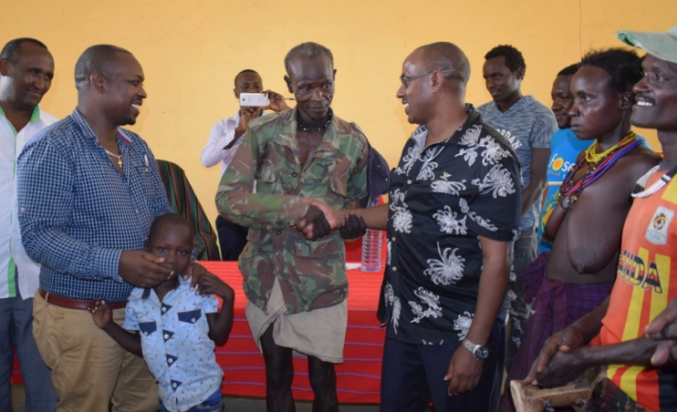 Turkana County Commissioner Stephen Ikua shaking hands with the father of the returned boy.