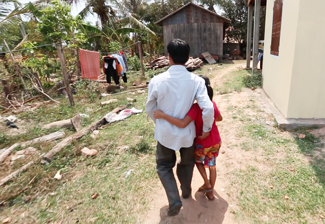 "Ly and his daughter at home in Kla Kropeu. ""This is our home. We know this land,"" Ly says."