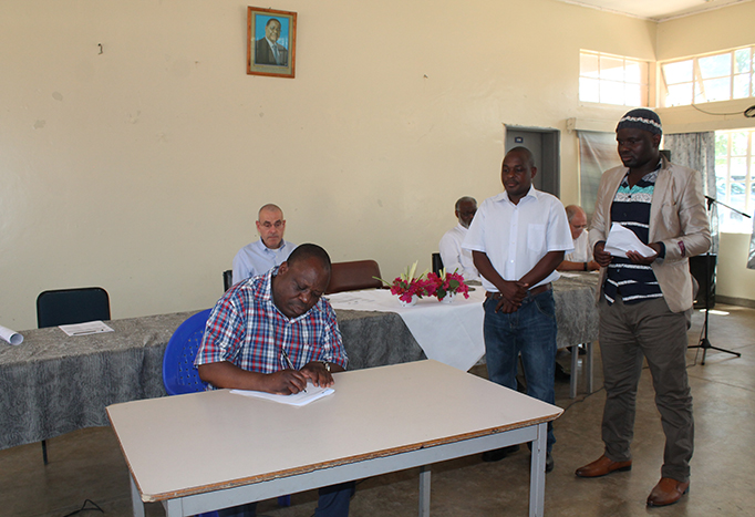 Dr. Friday Njaya of the Department of Fisheries signs the management agreement for Sub-Fisheries Association Mponda in Lake Malawi, while the chair of the association and a Traditional Authority representative look on.