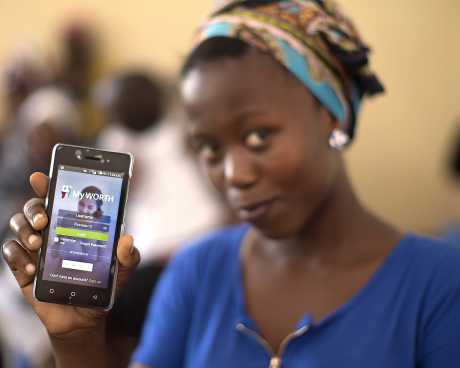 Young woman in Tanzania shows off her phone with the MyWORTH app.