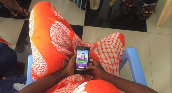 A young woman in Tanzania opens the MyWORTH app.