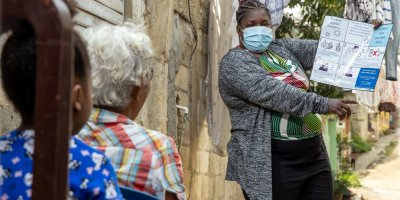 An ACHIEVE community volunteer promotes Covid-19 prevention measures in a community in Santo Domingo. Credit: USAID