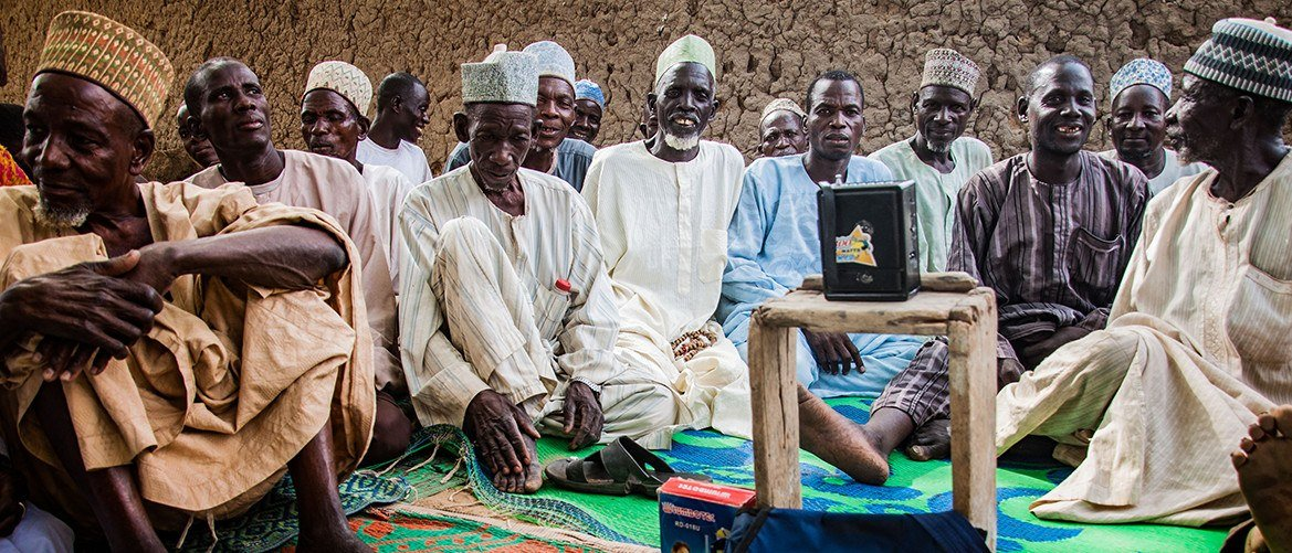 caption: In Nigeria, Pact is using radio listening groups to share important health messages. These men are members.
