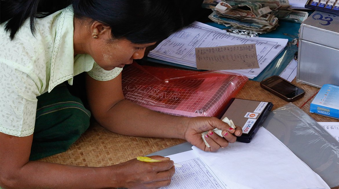 caption: A member of a Pact WORTH group in Myanmar reviews banking records.