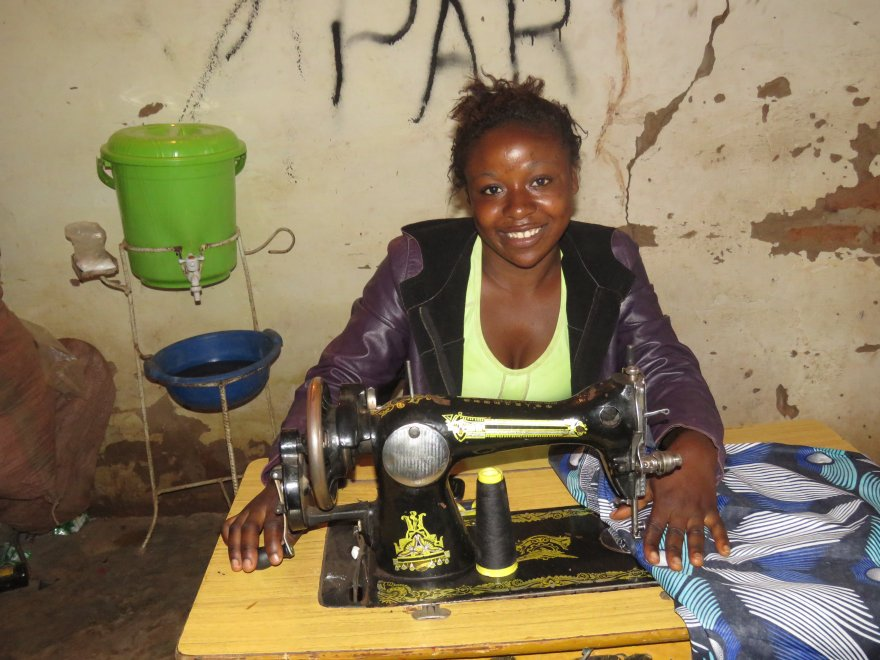Eliane sits at her sewing machine.